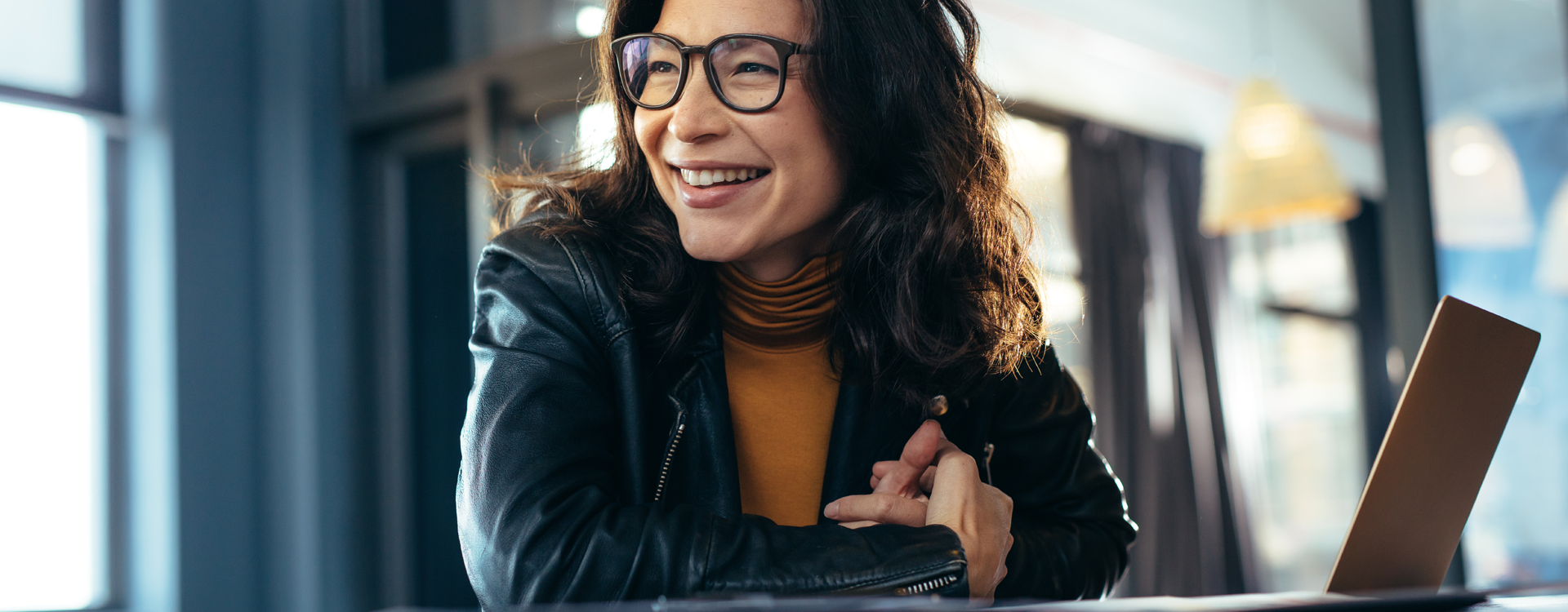 a woman wearing glasses, smiling and working on her laptop
