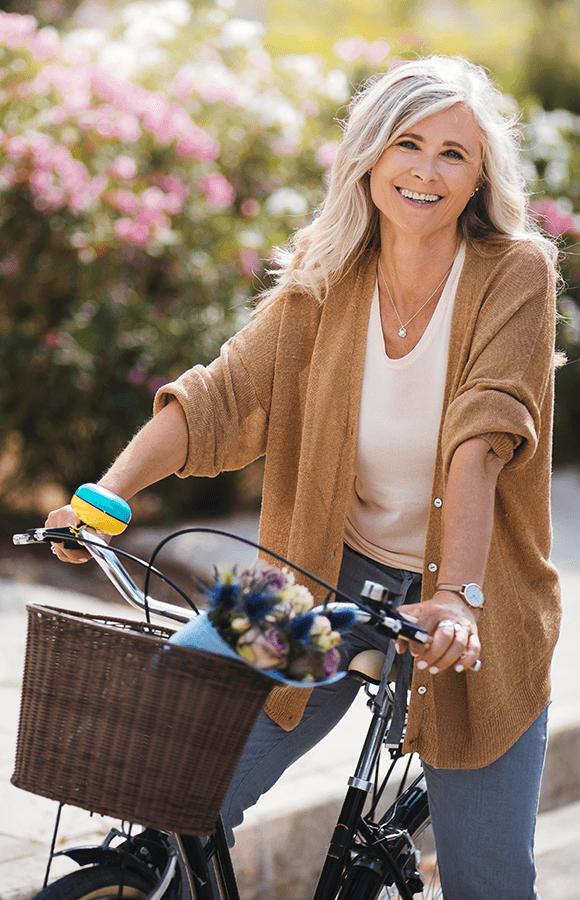 Woman riding a bike with flowers in the front basket