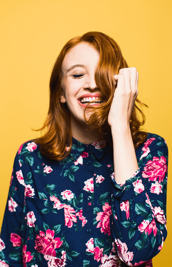 Red headed woman laughing and running hand through her hair