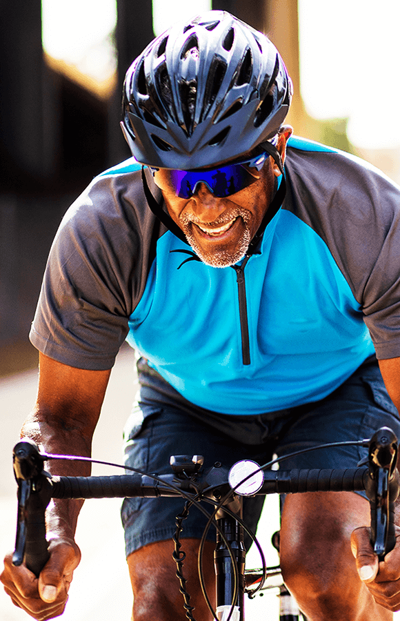 Man with sunglasses and helmet on riding a bike