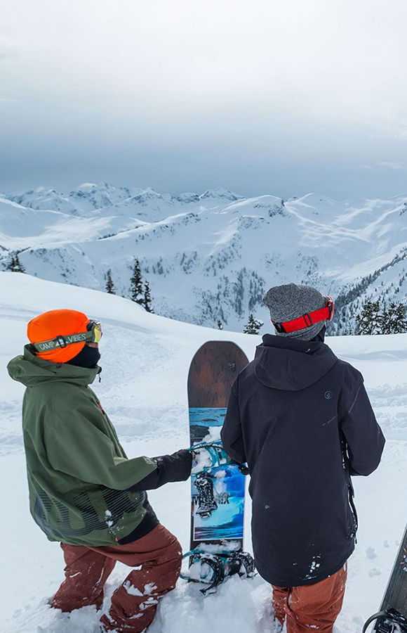 Two snowboarders on top of a mountain getting ready to snowboard down
