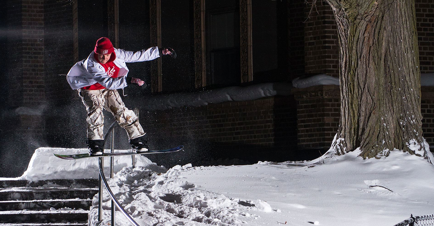 Snowboarder grinding on rail
