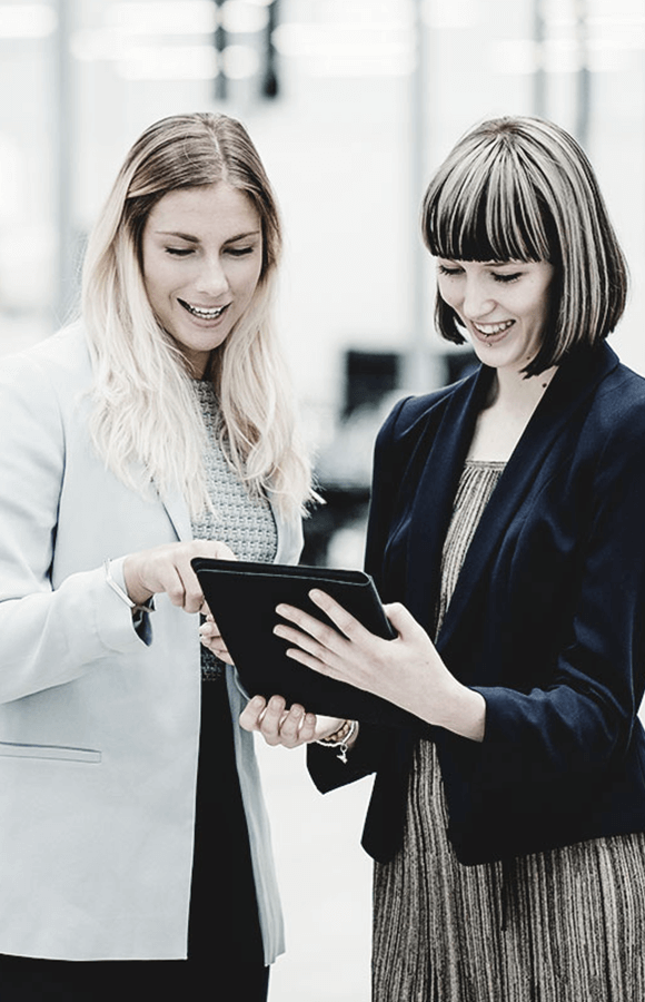 Two women looking at tablet and smiling